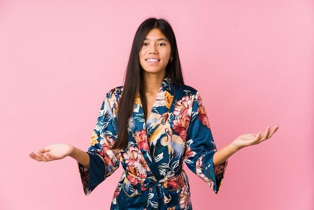 Giovane donna asiatica che indossa un pigiama di un kimono che mostra un'espressione benvenuta.