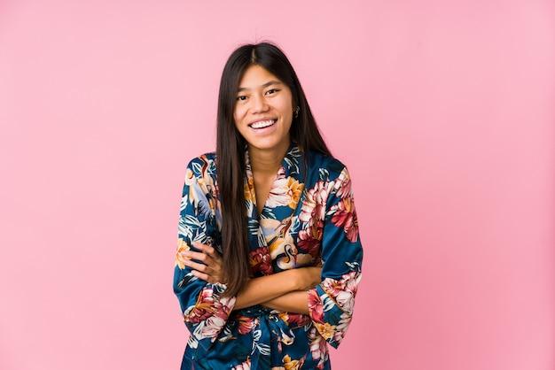Giovane donna asiatica che indossa un pigiama di un kimono che ride e che si diverte