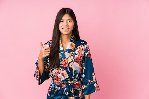 Giovane donna asiatica che indossa un pigiama di un kimono che sorride e che alza pollice in su