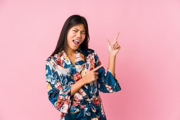 Giovane donna asiatica che indossa un pigiama kimono che punta con gli indici verso uno spazio di copia, esprimendo eccitazione e desiderio.