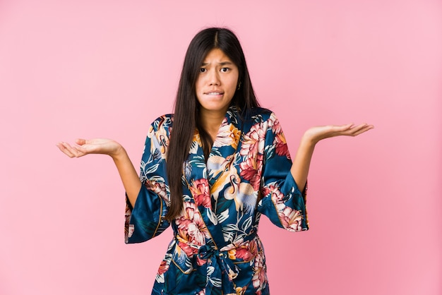 Giovane donna asiatica che indossa un pigiama kimono confuso e dubbioso scrollando le spalle le spalle per tenere uno spazio di copia.