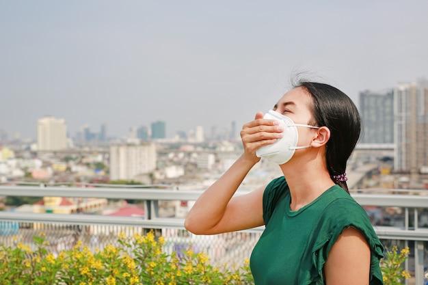 Giovane donna asiatica che indossa una maschera di protezione