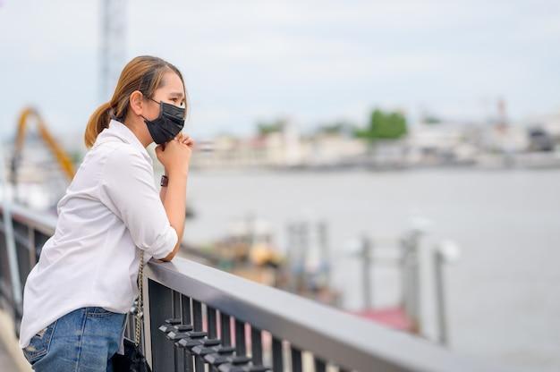 Giovane donna asiatica che indossa una maschera protettiva per prevenire la diffusione di germi e virus in città