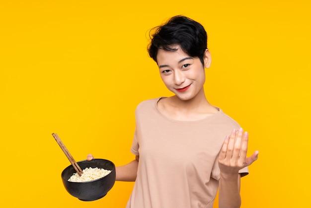 Giovane donna asiatica che invita a venire con la mano. felice che tu sia venuto con in mano una ciotola di noodles con le bacchette