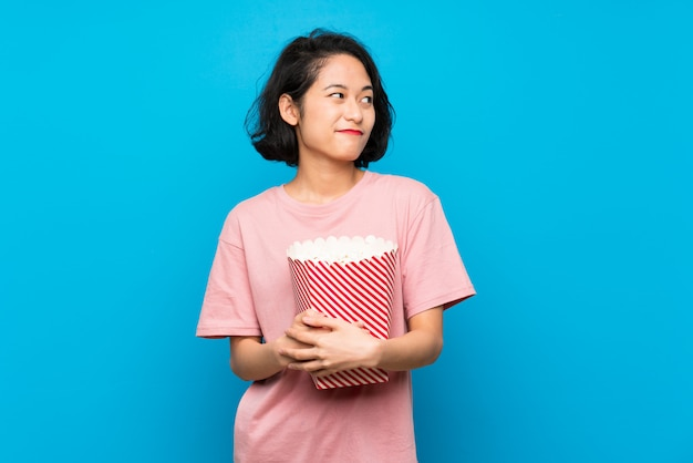 Giovane donna asiatica che mangia i popcorn che fanno gesto di dubbi mentre sollevando le spalle