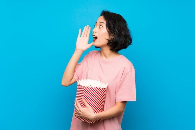 Giovane donna asiatica che mangia i popcorn che gridano con la bocca spalancata