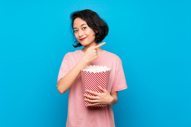 Giovane donna asiatica che mangia i popcorn che indicano il lato per presentare un prodotto