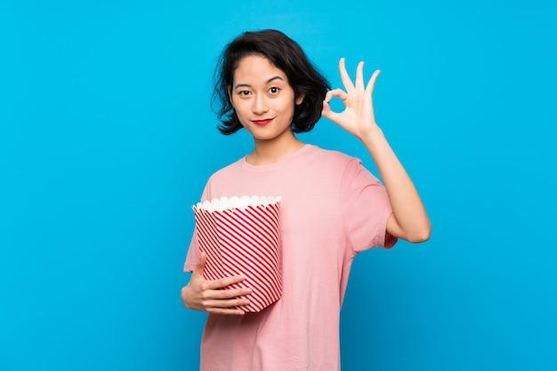 Giovane donna asiatica che mangia i popcorn che mostrano segno giusto con le dita