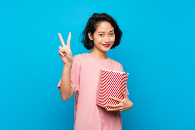 Giovane donna asiatica che mangia i popcorn che sorridono e che mostrano il segno di vittoria