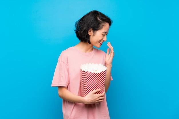 Giovane donna asiatica che mangia i popcorn che sorridono molto