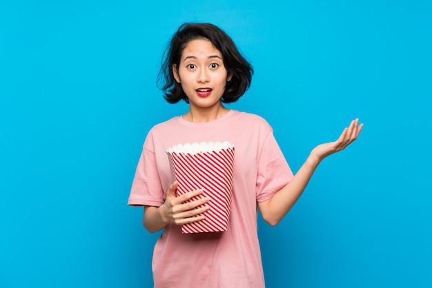 Giovane donna asiatica che mangia i popcorn con espressione facciale colpita