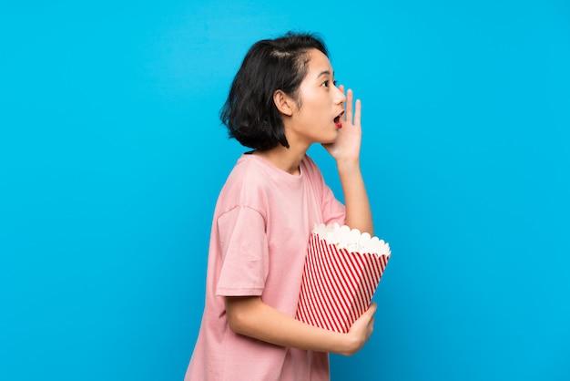 Giovane donna asiatica che mangia i popcorn