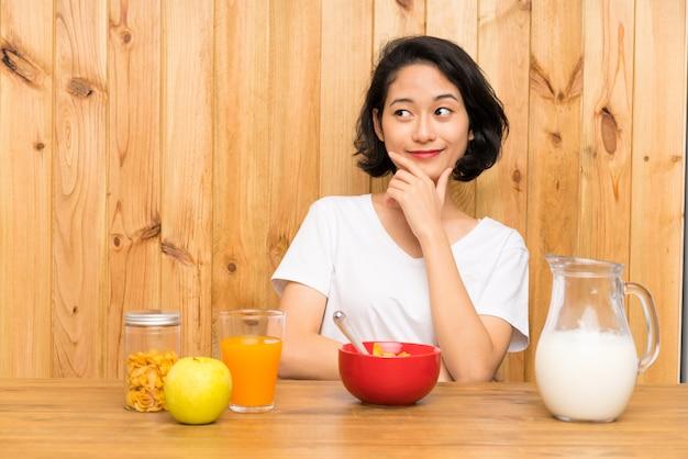 Giovane donna asiatica che mangia latte di prima colazione che pensa un'idea