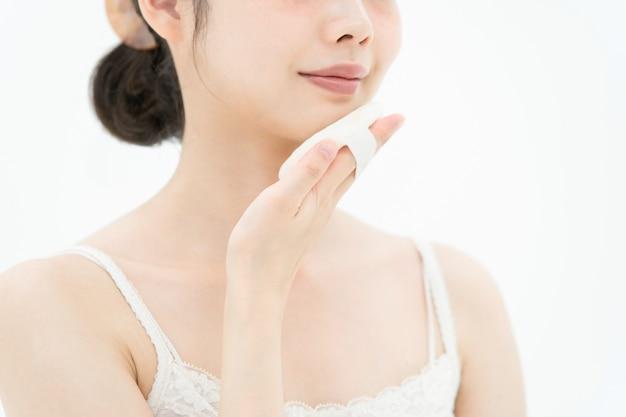 Giovane donna asiatica che mette soffio alla sua pelle facciale