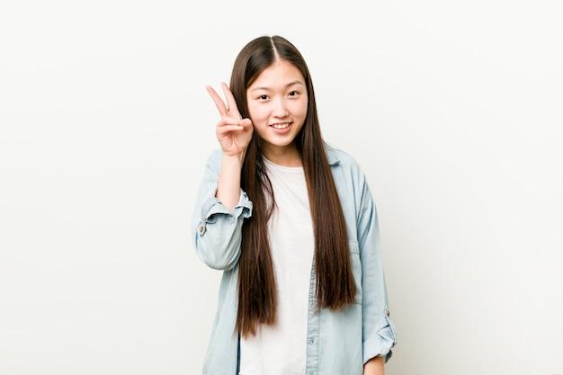 Giovane donna asiatica che mostra il segno di vittoria e che sorride ampiamente.