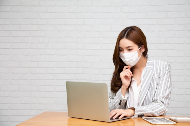 Giovane donna asiatica che per mezzo del computer portatile e indossando la maschera di protezione.