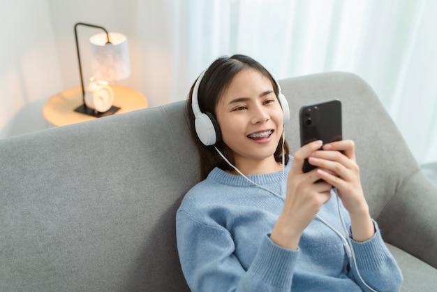 Giovane donna asiatica che per mezzo del suo telefono e ascoltando la musica