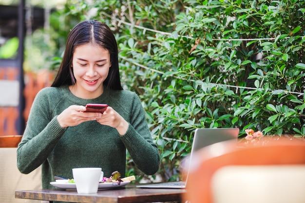Giovane donna asiatica che prende una foto della prima colazione