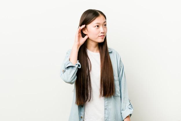 Giovane donna asiatica che prova ad ascoltare un gossip.