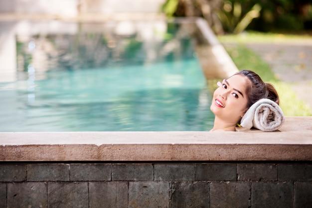 Giovane donna asiatica che si appoggia indietro con un asciugamano bianco