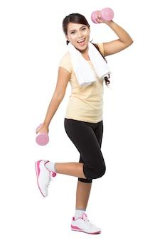 Giovane donna asiatica che si esercita, tenendo bilanciere, isolato
