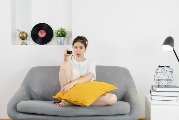 Giovane donna asiatica che si siede al sofà nella casa e che tiene il telecomando della tv per guardare i film in una giornata rilassante.