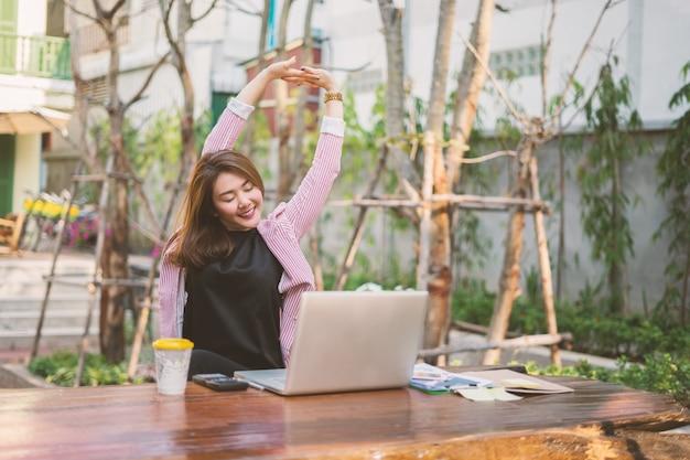Giovane donna asiatica che si siede al tavolo davanti al computer portatile