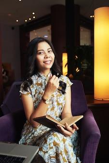 Giovane donna asiatica che si siede in poltrona in caffè con la penna e il giornale