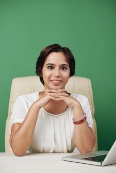 Giovane donna asiatica che si siede nella sedia dell'ufficio allo scrittorio con il computer portatile e che posa con le mani giunte