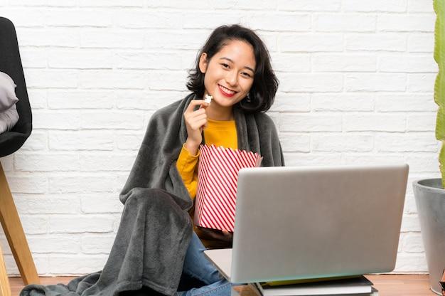 Giovane donna asiatica che si siede sul pavimento che mangia i popcorn