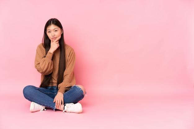 Giovane donna asiatica che si siede sul pavimento isolato sul pensiero rosa dello spazio