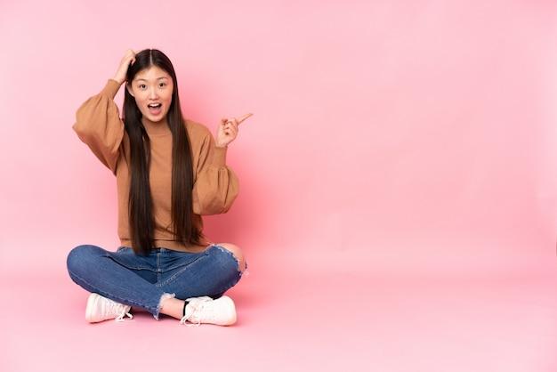 Giovane donna asiatica che si siede sul pavimento isolato sulla parete rosa sorpresa e che indica dito il lato