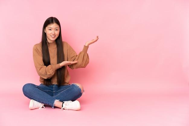 Giovane donna asiatica che si siede sul pavimento sulla parete rosa che estende le mani al lato per invitare a venire