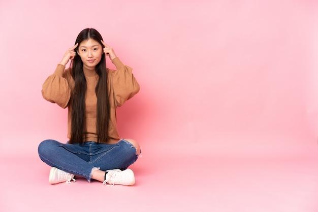 Giovane donna asiatica che si siede sul pavimento sulla parete rosa che ha dubbi e pensare