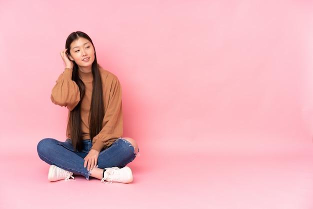 Giovane donna asiatica che si siede sul pavimento sulla parete rosa che pensa un'idea