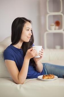 Giovane donna asiatica che si siede sul sofà che mangia caffè withpastry
