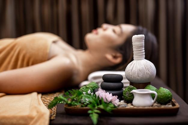 Giovane donna asiatica che si trova sul letto nel massaggio della stazione termale.