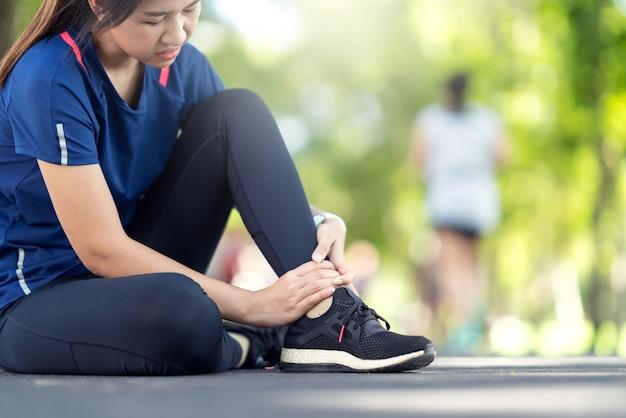 Giovane donna asiatica che soffre di infortunio alla caviglia.