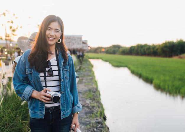 Giovane donna asiatica che sorride con la macchina fotografica ragazza che gode della bellissima natura con il tramonto. trav