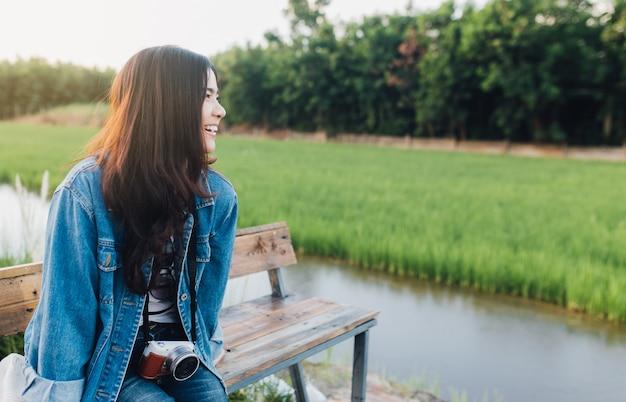 Giovane donna asiatica che sorride con la macchina fotografica ragazza che gode della bellissima natura con il tramonto.