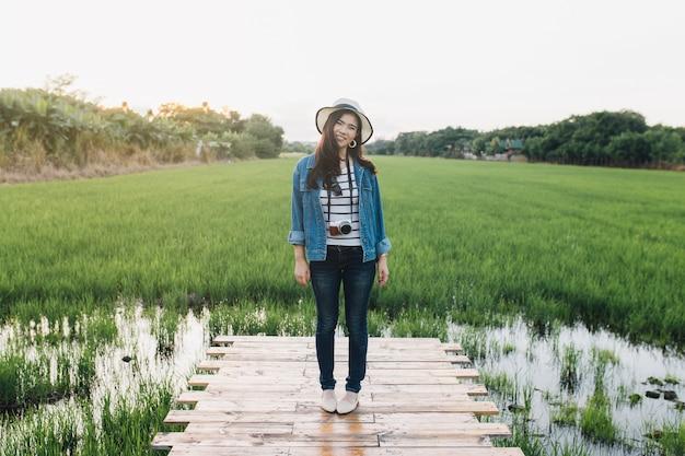 Giovane donna asiatica che sorride in cappello con la macchina fotografica. ragazza che gode della bellissima natura con il tramonto.