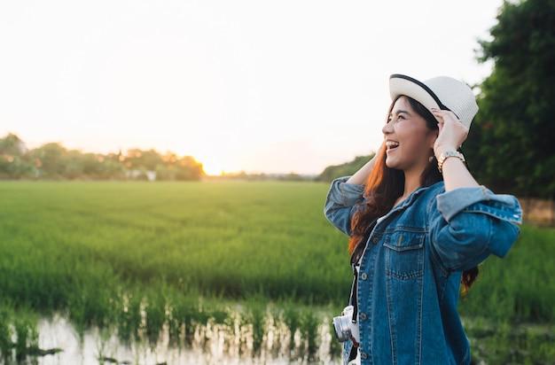Giovane donna asiatica che sorride in cappello ragazza che gode della bellissima natura con il tramonto.