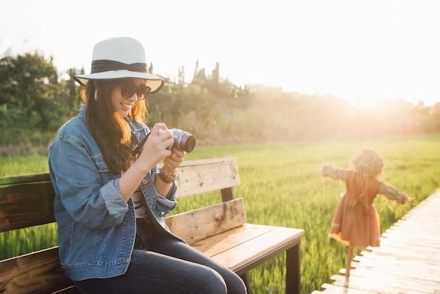 Giovane donna asiatica che sorride in cappello ragazza che usando la macchina fotografica e godendo