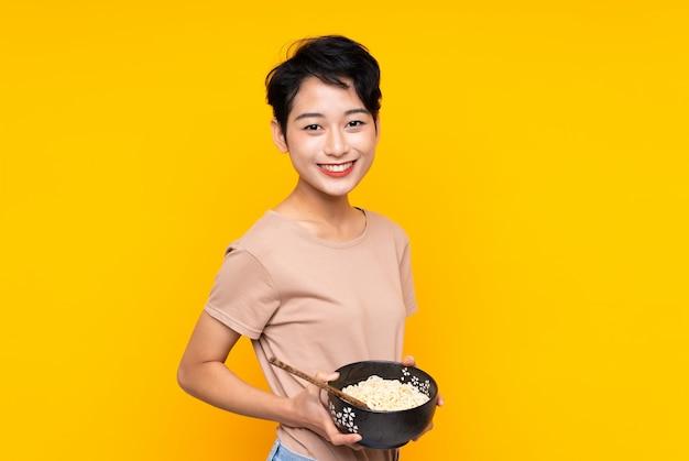 Giovane donna asiatica che sorride molto mentre tiene una ciotola di tagliatelle con le bacchette