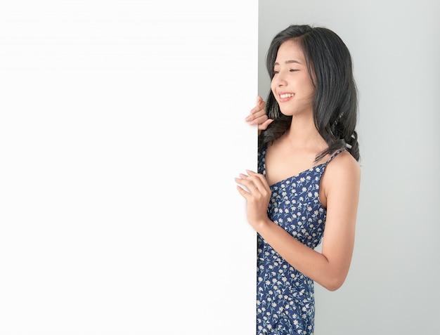 Giovane donna asiatica che tiene carta in bianco con il fronte e lo sguardo sorridenti