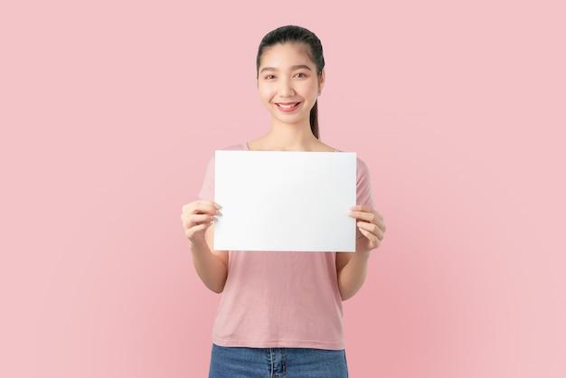 Giovane donna asiatica che tiene documento in bianco con il fronte sorridente e che osserva sull'azzurro.