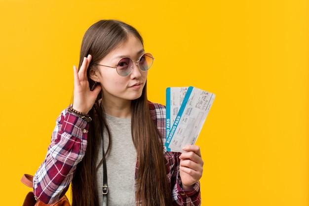 Giovane donna asiatica che tiene i biglietti aerei che provano ad ascoltare un gossip.