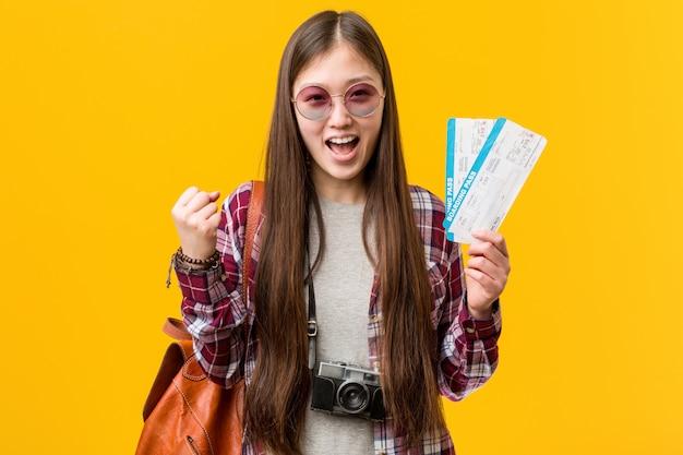 Giovane donna asiatica che tiene i biglietti aerei incoraggiare spensierato ed eccitato