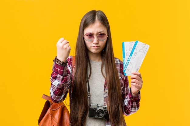 Giovane donna asiatica che tiene i biglietti di aria che mostrano pugno con con espressione facciale aggressiva.