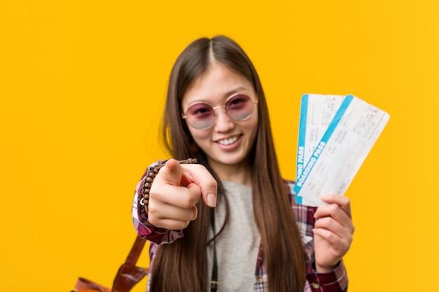 Giovane donna asiatica che tiene i sorrisi allegri dei biglietti aerei che indicano la parte anteriore.